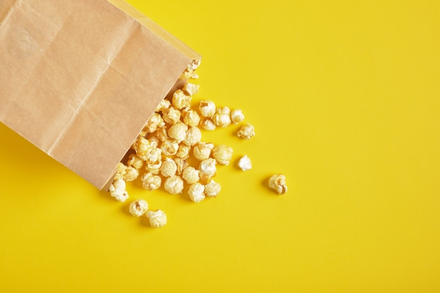 Popcorn in papieren verpakkingen op een gele achtergrond kopie ruimte