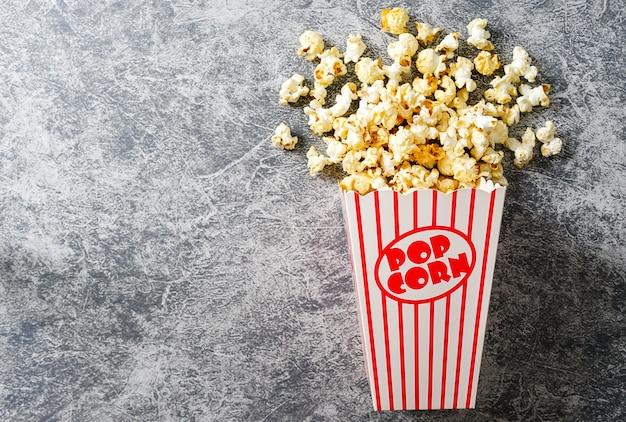 Popcorn in rood en wit karton op loft achtergrond bovenaanzicht plat lag