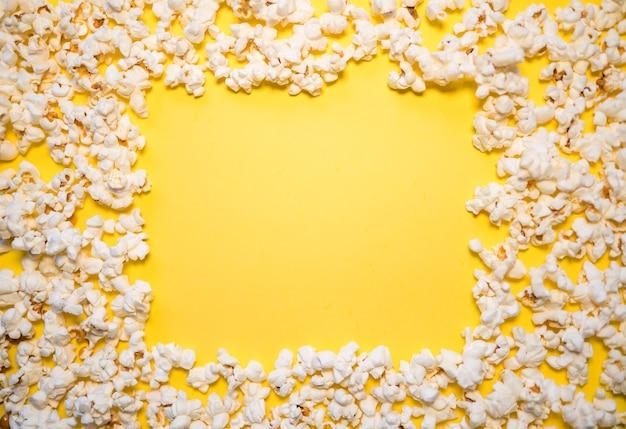 Popcorn met een gele achtergrond en kopieer ruimte