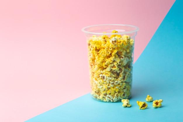 Popcorn op een gekleurde achtergrond. minimaal voedselconcept. entertainment, film- en video-inhoud. esthetiek jaren 80 en 90 concept