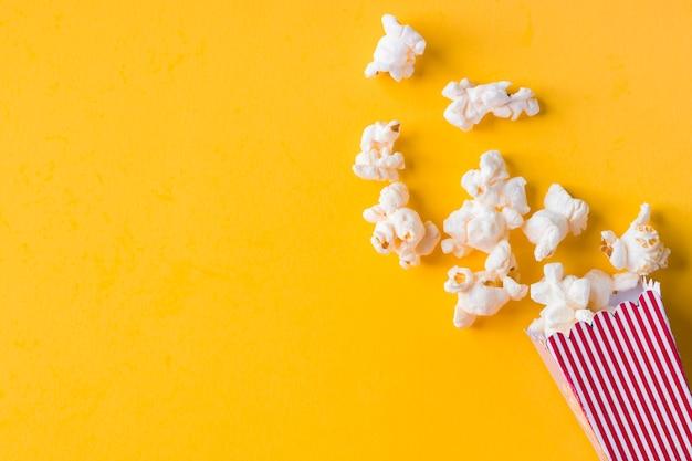 Popcorn op gele achtergrond met kopie ruimte