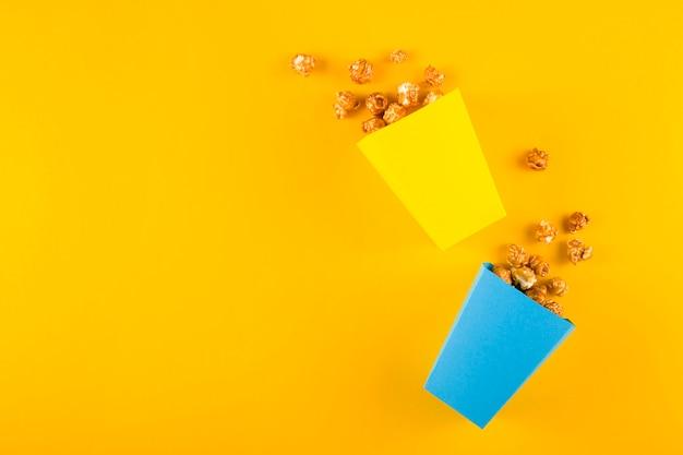 Popcorn voor thuisbioscoop op gele tafel. bovenaanzicht