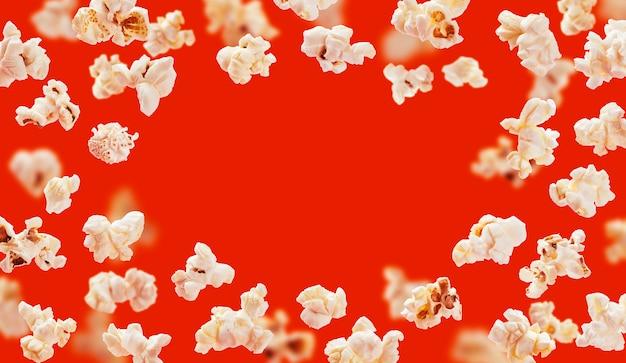 Popcornframe, vliegende die popcorn op rood wordt geïsoleerd