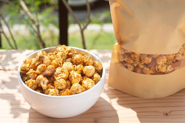 Popcornkaramel op witte kom op houten lijst.