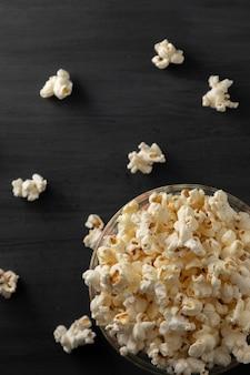 Popcornkom omgedraaid op een zwarte houten tafel popcorn verspreid over de tafel