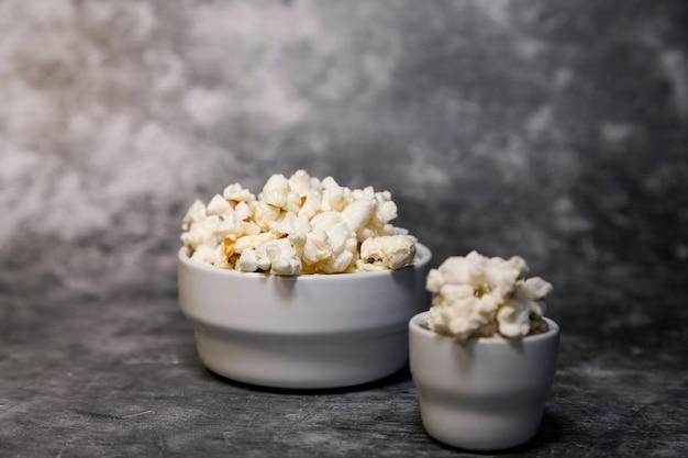 Popcornkommen op een grijze achtergrond. horrorfilms kijken.