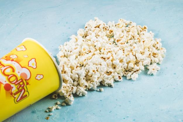 Popcorns verspreid over de blauwe tafel uit de gele container