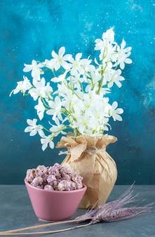 Popcornsuikergoed in een kom, paarse tarwestengels en witte lelies in een vaas op blauwe achtergrond. hoge kwaliteit foto