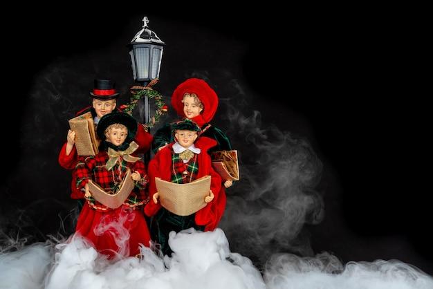 Poppenfamilie die kerstliederen in de nacht met mistige rook zingen.