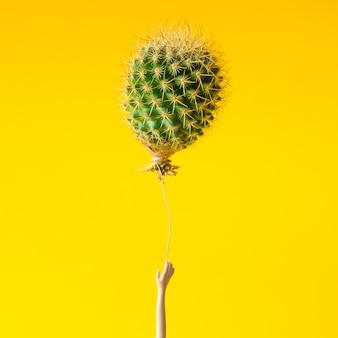 Poppenhand die voor cactusballon op geel reikt