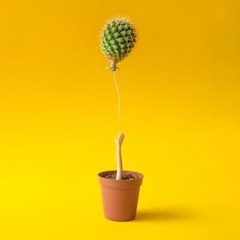 Poppenhand die voor cactusballon reikt uit bloempot op geel.