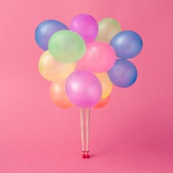 Poppenpoten met kleurrijke ballonnen op pastelroze ondergrond