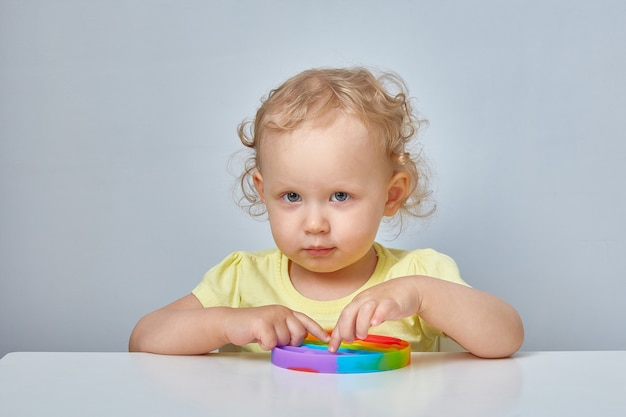 Populair antistress speelgoed pop it. kind spelen met de pop it fidget toy. gelukkige jeugd, populaire educatieve spelletjes.