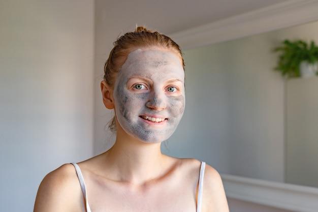 Populair spa-behandeling borrelend masker met houtskoolzuurstofzuiverend product op het gezicht van mooi meisje met groene ogen, schoonheidsbehandelingen thuis