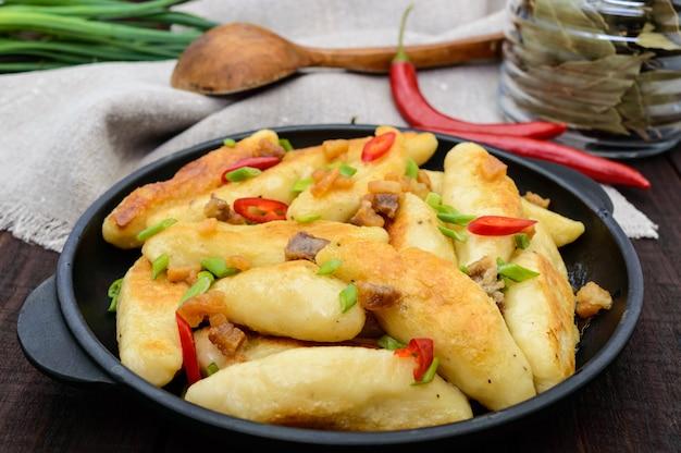 Populair traditioneel tsjechisch, hongaars, duits gerecht aardappel knedli (dumplings) met plakjes gebakken spek, pittige rode peper en groene uien