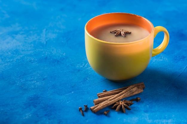 Populaire aziatische opwarmende drank masala thee in een gele beker met koriander, kaneel en rozenstengel op een klassieke blauwe achtergrond.
