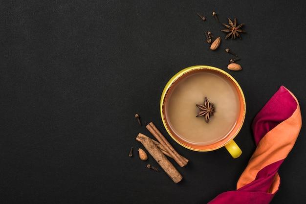 Populaire aziatische opwarmende drank masala thee in een gele beker met koriander, kaneel en rozenstengel op een zwarte achtergrond.
