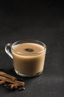 Populaire aziatische opwarmende drank masala thee in een helderglazen beker met koriander, kaneel en rozensteel op een zwarte achtergrond.