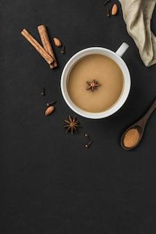 Populaire aziatische opwarming van de aarde masala thee drinken in een witte kop met koriander, kaneel en rozenstengel op een zwarte achtergrond.
