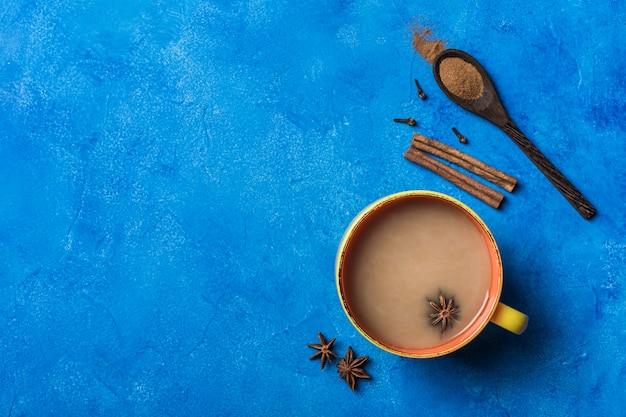 Populaire aziatische opwarmingsdrank masala thee in een gele ñ up met koriander, een houten lepel met kaneel en een rozensteel op een klassieke blauwe achtergrond.