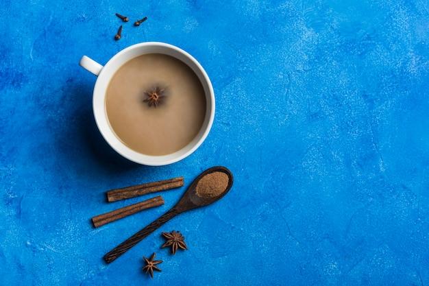 Populaire aziatische opwarmingsdrank masala thee in een witte with up met koriander, een houten lepel met kaneel en een rozensteel op een klassieke blauwe achtergrond.