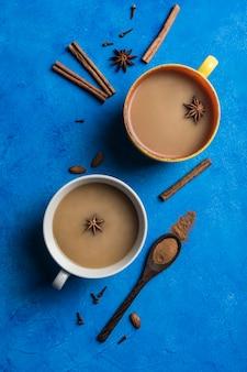 Populaire aziatische opwarmingsdrank masala thee in twee kopjes met koriander, een houten lepel met kaneel en een rozensteel op een klassieke blauwe achtergrond.