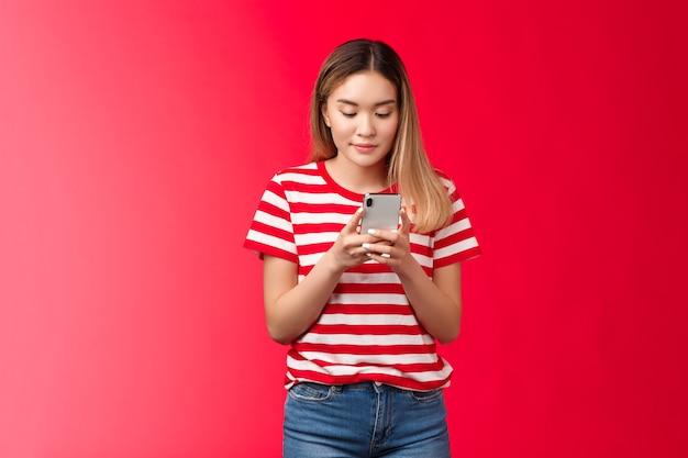 Populaire aziatische vrouwelijke lifestyle blogger die foto online plaatst houd smartphone kijk telefoon display scroll...