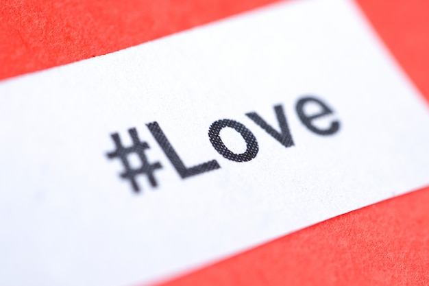 Populaire hashtag 'love' gedrukt op wit vel papier op rood