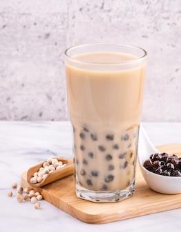 Populaire taiwan drankje - bubble melkthee met tapioca parelbal in drinkglas op marmeren witte tafel houten dienblad achtergrond, close-up, kopie ruimte