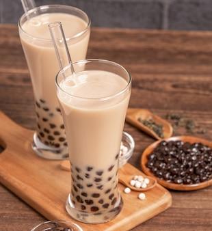 Populaire taiwanese drank - bubble melkthee met tapioca parelbal in drinkglas en stro, houten tafel grijze bakstenen achtergrond, close-up, kopie ruimte