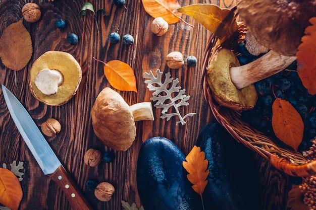 Porcinipaddestoelen in mand met bessen en noten op houten lijst. herfstoogst met schoenen. verzameld herfstgewas