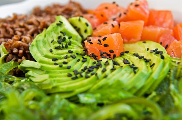 Porkom. ingrediënten: zalm, avocado, bruine rijst, algen.