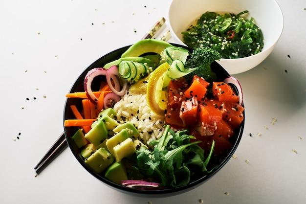 Porkom met zalm, avocado, eetstokjes die over witte achtergrond worden geïsoleerd. bovenaanzicht