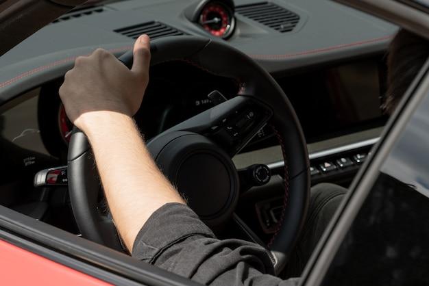 Porsche autodashboard. porsche-autostuurwiel en vrouwelijke hand.