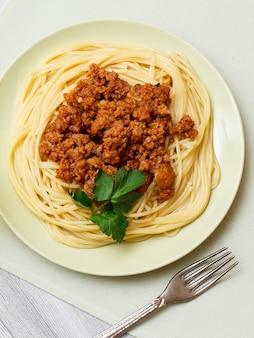 Porseleinen bord met spaghetti bolognese en peterselie bladeren, vork en servet op grijze houten planken. bovenaanzicht.