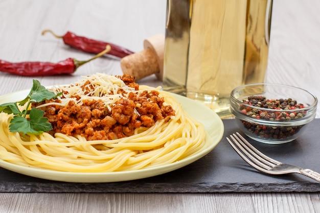 Porseleinen bord met spaghetti en bolognese souce, kom met pimentbessen, rode pepers en fles witte wijn op de achtergrond.