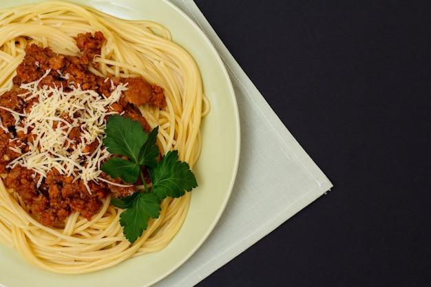Porseleinen bord met spaghetti en bolognesesaus op keukenservet en zwarte achtergrond. bovenaanzicht.