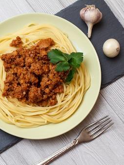 Porseleinen bord met spaghetti en bolognesesaus, ui en knoflook op een zwart stenen bord. bovenaanzicht.