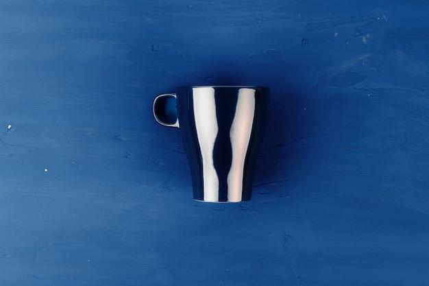 Porseleinen koffiekopje op klassieke blauwe achtergrond, bovenaanzicht