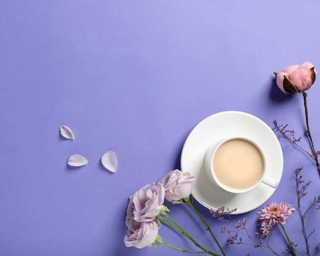Porseleinen kopje met koffie en mooie lila rozen, gedroogde bloemtakken op een lila achtergrond. lente koffie concept. plat lag stijl, bovenaanzicht, plaats voor tekst