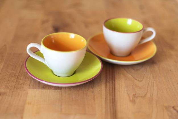 Porseleinen kopjes en plaat op de houten keukentafel