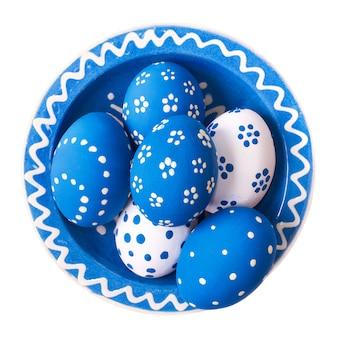 Porseleinen plaat van blauwe en witte ester-eieren op wit