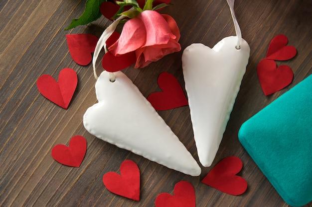 Porseleinen witte harten met roze roos en blauwe doos op de tafel.
