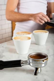 Portafilter met gemalen koffie en drie kopjes koffie