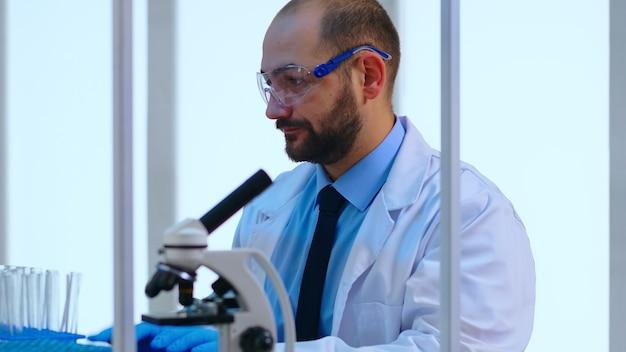 Portait van scheikundige typen op computer die virusontwikkeling controleert in modern uitgerust laboratorium. arts die werkt met verschillende bacteriën, weefsel- en bloedmonsters, farmaceutisch onderzoek naar antibiotica