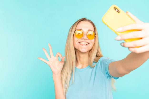 Portarit van glimlachend meisje zelfportret schieten op de camera aan de voorkant van de smartphone die zich voordeed op blauw