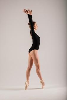 Portarit van sensuele professionele blanke callet danser in pak en pointes schoenen poseren op de vloer op wit.