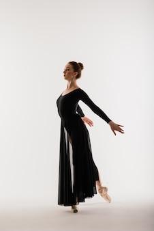 Portarit van sensuele professionele kaukasische callet-danser in pak en pointes-schoenen op wit.