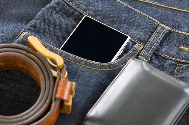 Portemonnee en smartphone op denim jeans