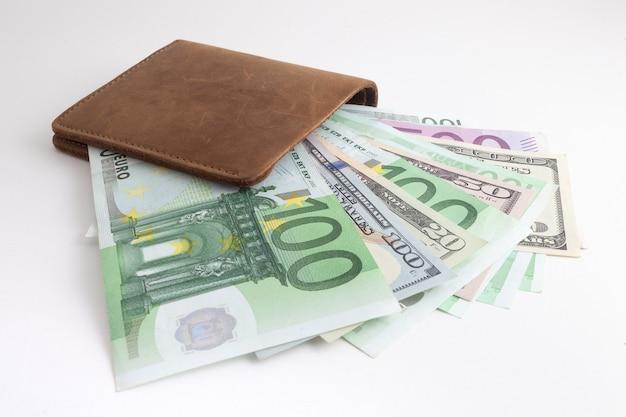 Portemonnee met euro en dollars die eruit steken, geïsoleerd